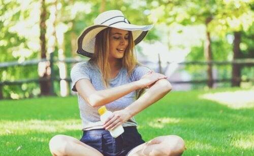 Une femme qui s'applique de la crème solaire.