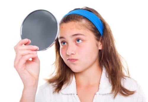 Une adolescente se regardant dans un miroir.