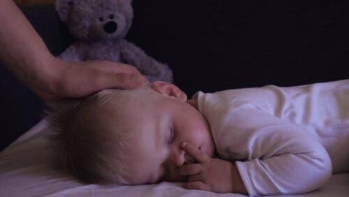 Un bébé en train de dormir avec sa mère qui le caresse.