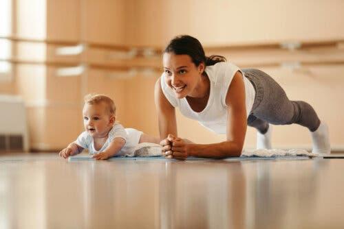 Un bébé imitant sa maman qui fait du sport.