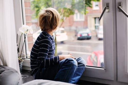 Un enfant souffrant de trouble de l'autisme qui regarde par la fenêtre.