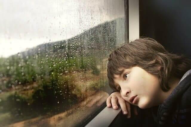 Un enfant fatigué regardant par la fenêtre.