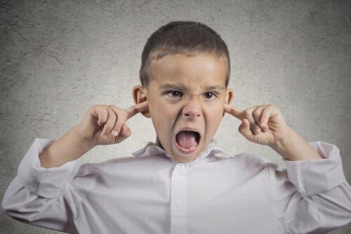 Un enfant se bouchant les oreilles