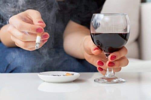 Une femme buvant un verre de vin et fumant