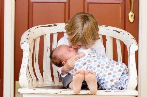 Un enfant embrassant un bébé.