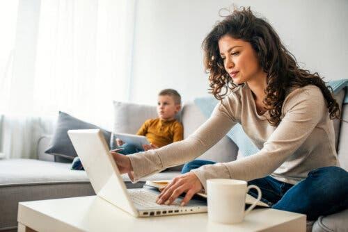 Une mère sur son ordinateur et son fils devant la télévision.