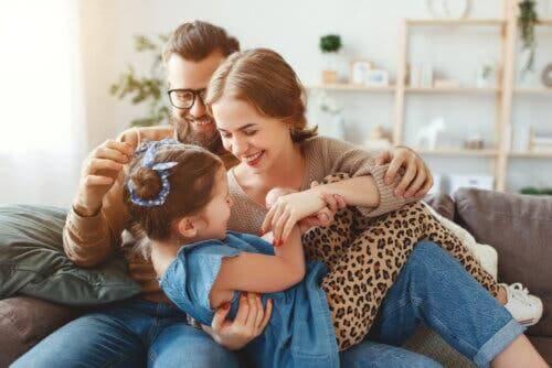 Des parents chatouillant leur fille.