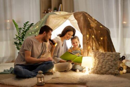 Des parents et une fille lisant sous une tente.