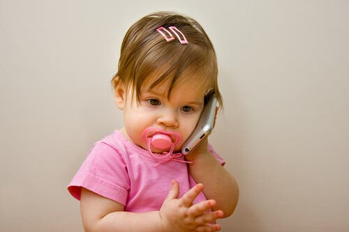 Une petite fille qui veut parler au téléphone