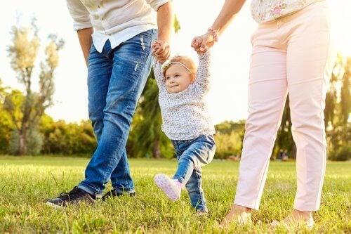 bébé qui marche avec ses parents