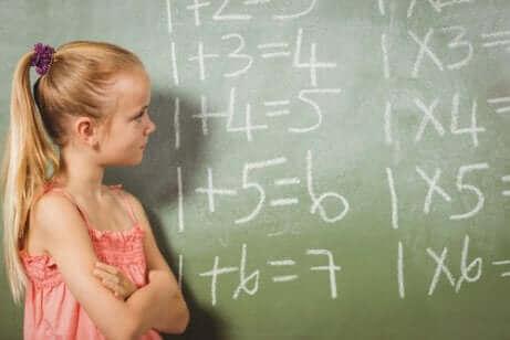 Une jeune fille devant un tableau noir avec des opérations mathématiques.