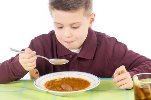 Un enfant qui mange une soupe.