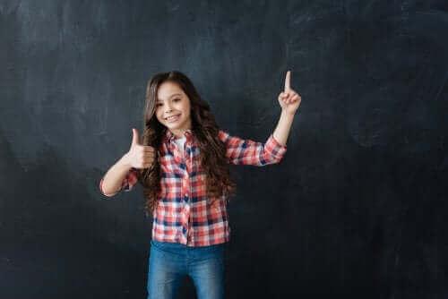 Une jeune fille souriant devant un tableau noir.