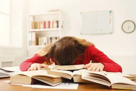 Une fille endormie sur des livres.
