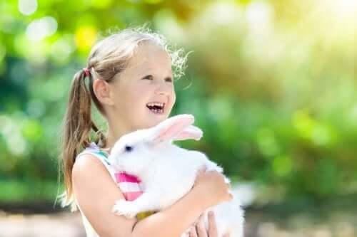 Une petite fille serre son lapin dans ses bras.