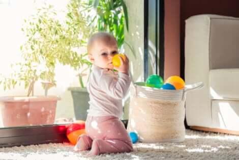 Un bébé avec un panier à jouets.