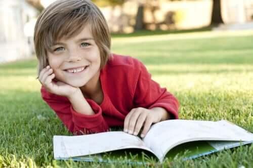 enfant lisant un livre dans l'herbe