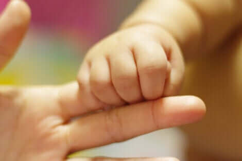 La main d'un bébé qui attrape celle de sa maman.