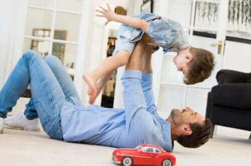 Un père jouant avec son fils avec une voiture en jouet dans le salon de la maison.