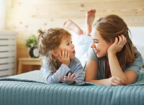 Une mère et sa fille discutant sur un lit.