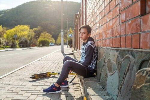 Un adolescent avec son skate qui ressent la solitude.