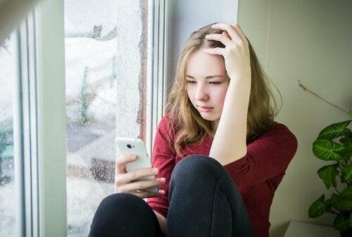 Une adolescente avec son portable sur les réseaux sociaux.