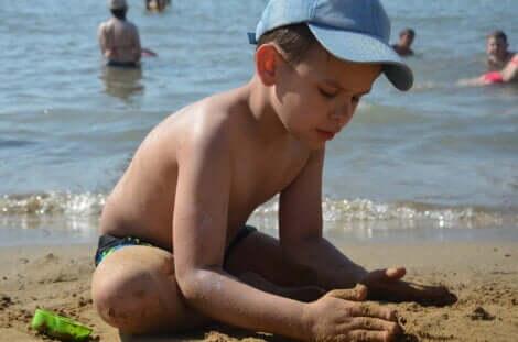 Un garçon qui joue dans le sable à la plage.