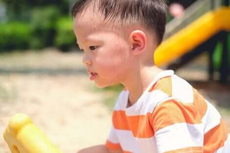 Un jeune garçon qui joue et transpire à la tête.