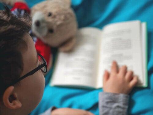 Un enfant en train de lire un livre avec des lunettes et sa peluche.