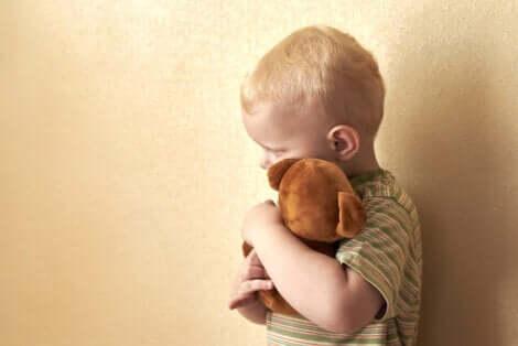 Un enfant qui fait un câlin à une peluche.