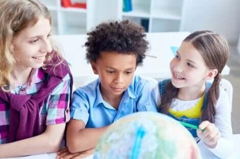 Enfants en classe qui regardent un globe terrestre.