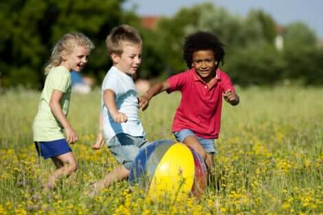 Trois enfants qui jouent avec un ballon.