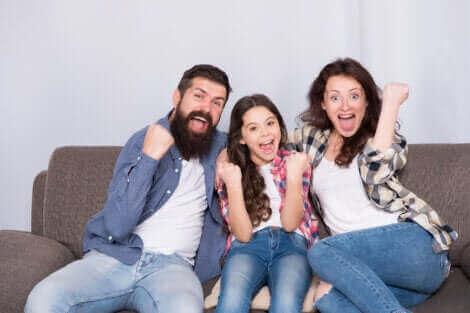 Une famille s'amusant sur leur canapé.