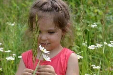 Une fille jouant avec des fleurs.