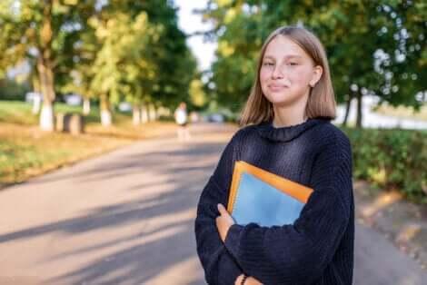 Une adolescente qui sourit avec des livres dans les bras.