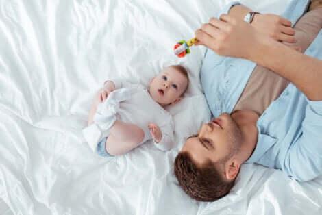 Un papa qui joue avec un hochet et son bébé.