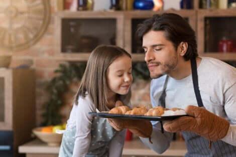 Un père et sa fille qui sentent des gâteaux sortant du four.