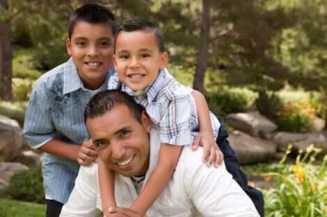 Un père et ses deux fils qui échangent un câlin.