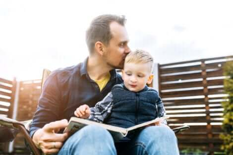 Un père qui lit un livre avec son enfant sur les genoux.