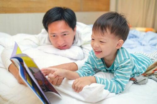 Un père et son fils lisant un livre allongés sur le lit.