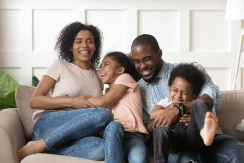 Une famille rit sur son canapé.