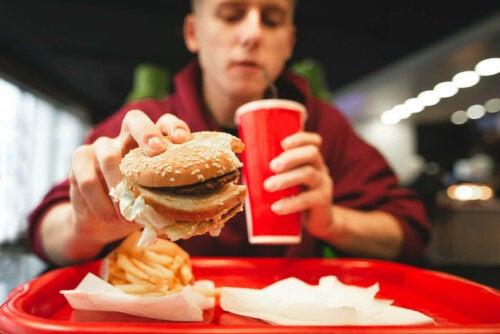 adolescent qui mange dans une restauration rapide ou fast-food