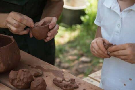 Un adulte et un enfant qui jouent avec l'argile.