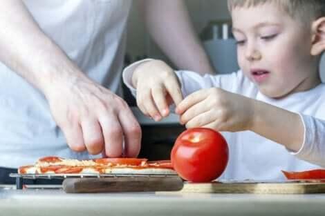 Un jeune enfant qui met des tomates sur une pizza.