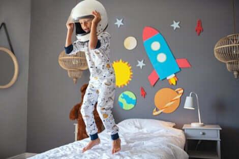 Un enfant qui saute sur son lit avec un casque sur la tête.