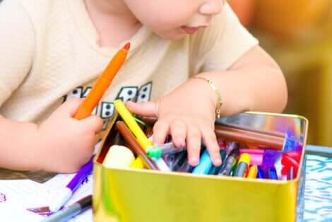 Un enfant qui fait un dessin avec des feutres.
