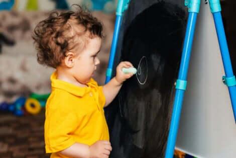 Un enfant qui écrit sur un tableau.