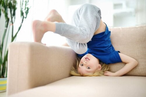 Un enfant impulsif faisant une roulade sur le canapé.