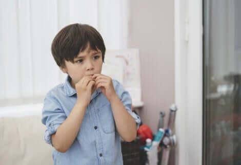 Un jeune enfant inquiet qui se mange les doigts.