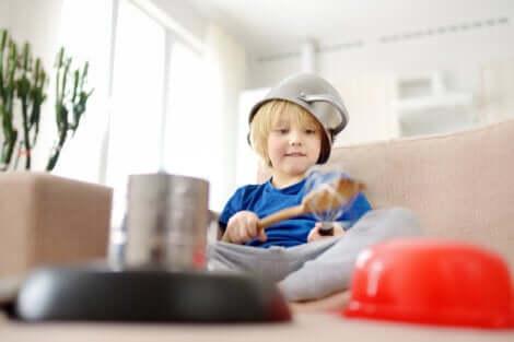 Un enfant qui joue des instruments de musique dans la cuisine.